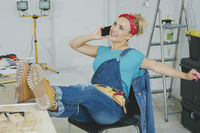 Relaxed female at workbench talking on smartphone