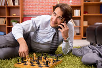 Young handsome boss playing chess during break