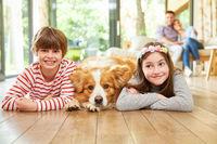 Kinder liegen zusammen mit Hund auf Parkett