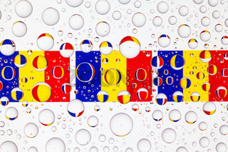 Water drops on glass and flags of Romania