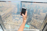 Girl tourist with mobile phone by the window of skyscraper of the Burj Khalifa in Dubai