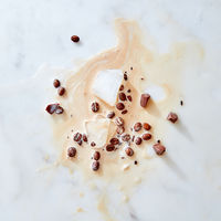 A pattern of splashes of coffee with milk pieces of chocolate, ice and coffee grains on a gray marble background with space for text. Flat lay