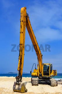Yellow excavator over sand