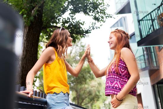 teenage girls or friends talking in summer city