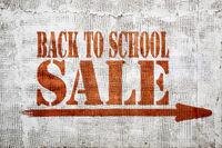 back to school sale graffiti on stucco wall