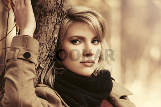 Sad young blond fashion woman in beige classic coat outdoors