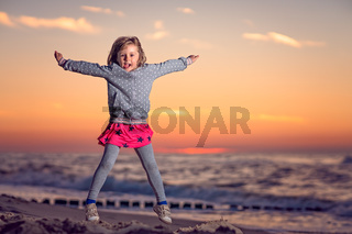 Girl jumping in the air on the beach