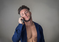 Muscular young man at home talking on cell phone