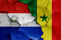 flags of Paraguay and Senegal painted on cracked wall