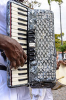 Musician hand playing accordion at popular religious festival