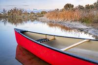 red canoe on a lake shore