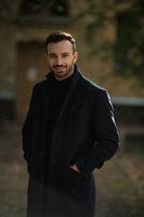 handsome smiling man in black coat