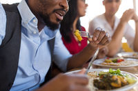 african man eating with friends at restaurant