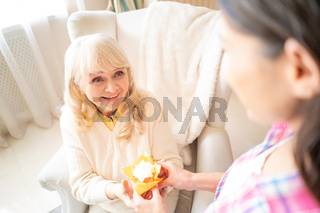 Charming daughter gives small birthday cupcake with candle to her senior mother