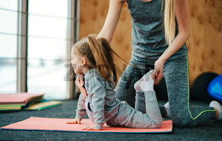 A little girl repeats exercises for her mother