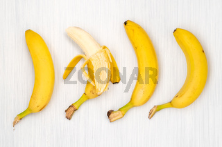 Four bananas on wooden table
