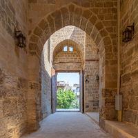 Passage at Al-Muayyad Bimaristan (hospital) historic building with stone bricks wall, arches, and entrance door, Cairo, Egypt