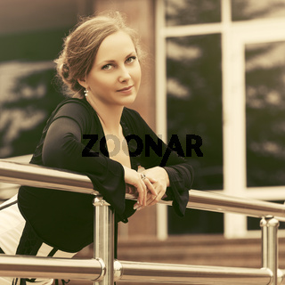 Happy beautiful fashion woman in black blouse leaning on railing
