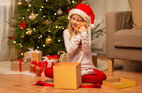 smiling girl in santa hat with christmas gift