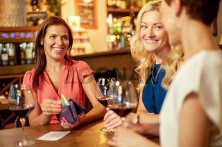 women paying bill at wine bar or restaurant