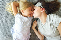 Cute loving emotional woman hugging her daughter tight while spending the morning in bed and feeling happy. Nose to nose