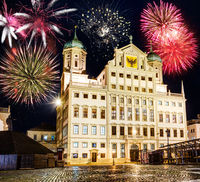 Fireworks at the illuminated town hall of Augsburg at night