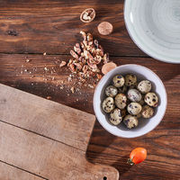 A bowl with quail eggs, pieces of walnut and a wooden board on the kitchen table with copy space. Ingredients for Healthy Salad. Flat lay