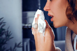 Sick woman holds white handkerchieif while sneezing