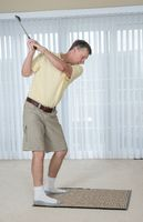 Senior adult man practicing golf grip and swing in bedroom