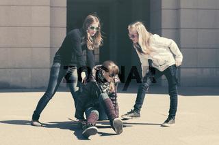 Happy teen girls with skateboard in city street