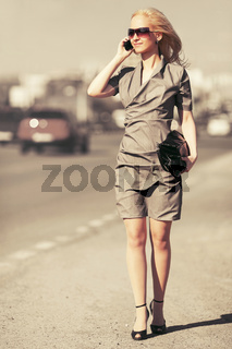 Young fashion blond woman calling on cell phone walking in city street