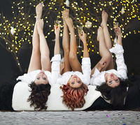 Smiling women in white shits with glasses of champagne over lights background