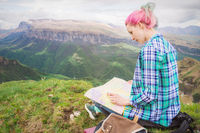 Girl traveler with multi-colored hair sitting on nature reading card and holding a compass in hand. The concept of navigating the search and tourism in the mountains. Travel Concept