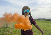 Imagination, Little boy wearing helmet and aircraft googles standing on a green field with colorful smoke, pretending to be a pilot