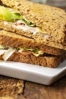 Nahaufnahme eines Schinken-Sandwiches auf Holz