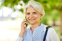 senior woman calling on smartphone in summer