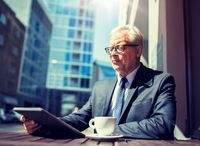 senior businessman with tablet pc drinking coffee