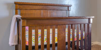 Varnished wooden crib inside a nursery