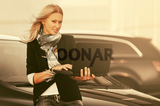 Young fashion business woman using laptop next to her car on parking