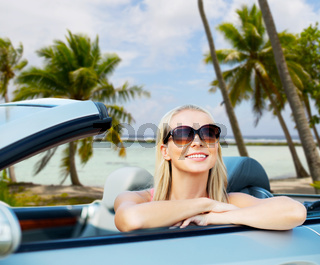 happy young woman in convertible car over beach