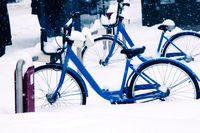 City bikes in the Parking lot covered with snow
