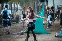 Young woman juggling with two hula hoops at the Lost Theory psytransce music festival held in Riomalo de Abajo