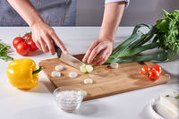 Fresh leek slices cut into the hands of a female cook on a wooden board on the kitchen table around a variety of organic vegetables. Cooking Healthy Salad