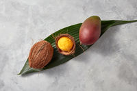 A mango ice cream ball in a coconut shell on a green leaf on a gray concrete background. Top view
