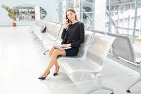 Geschäftsfrau mit Laptop telefoniert mit dem Handy