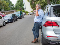 Man is standing in the street next to car and talking on the phone