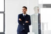 smiling businessman at office glass wall