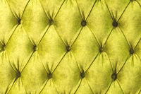 Velor surface of sofa close-up. Training equipment-velor mats tightened with buttons. Yellow chesterfield style quilted upholstery background close up
