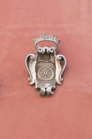 Carrara, Tuscany - Italy. The emblem of the city, made of marble, on the facade of a historic building.