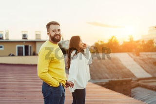 Loving young couple is standing on the roof of the house.